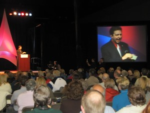 Atlanta magician and keynote speaker Joe M. Turner presents an illusion via IMAG at a 2010 conference.